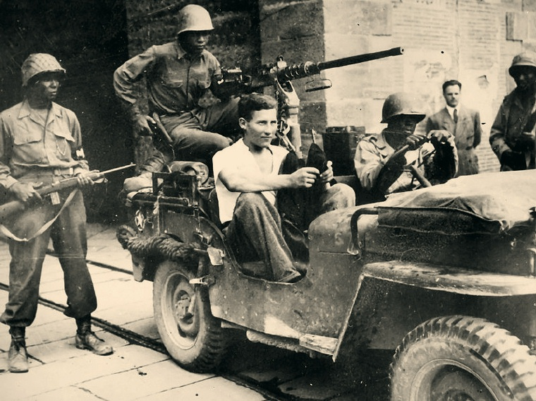 92nd Division troops escorting a German POW